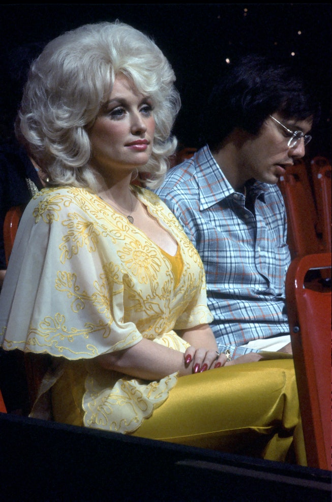 Dolly Parton with blonde hair and a yellow outfit in 1975.