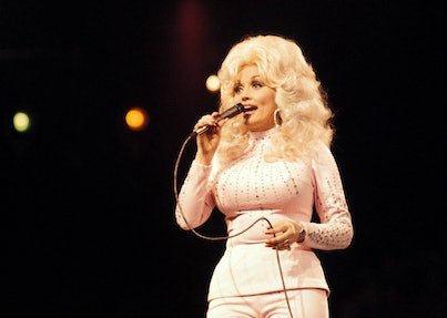 Dolly Parton on stage with big blonde hair and pink matching outfit in 1975.