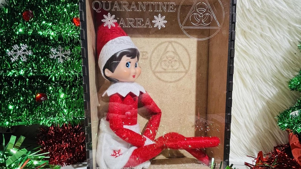 An Elf on the Shelf sits in a quarantine Christmas box from Etsy, surrounded by tinsel Christmas trees.