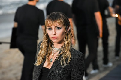 Miley Cyrus, with long hair and bangs, poses for a photo