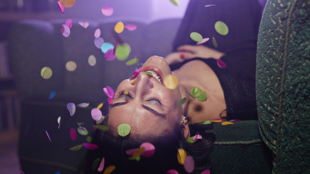 Young woman laying on sofa with confetti falling
