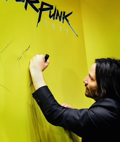 Keanu Reeves autographing a wall for Cyberpunk 2077.