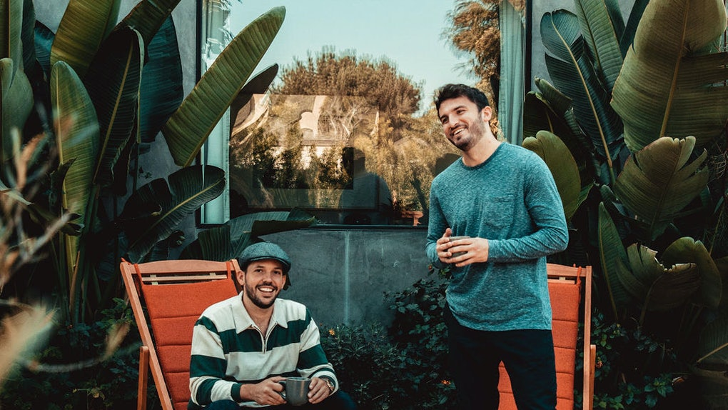 Vlog Squad's Zane Hijazi and Heath Hussar laugh while sitting and standing in front of greenery outdoors.