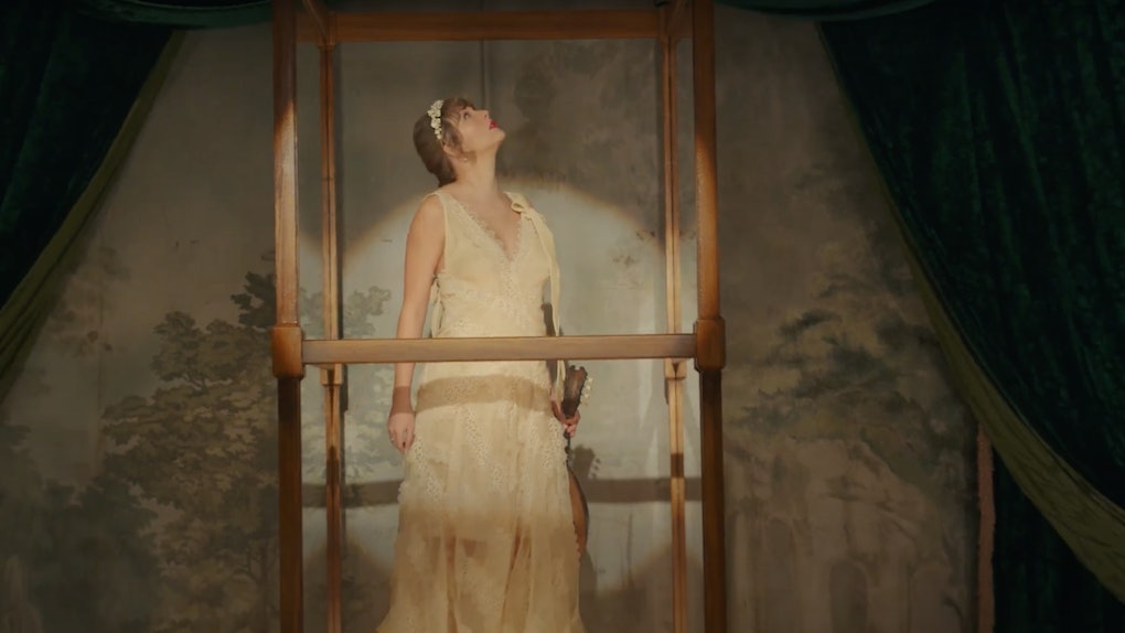 """Taylor Swift stands in a glass box while wearing a white dress and holding a ukulele in the """"willow"""" music video."""