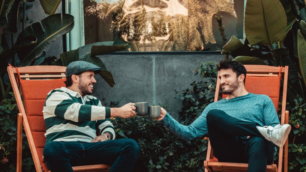 Vlog Squad's Zane and Heath sit in chairs and toast their coffee mugs while promoting their new brand Kramoda Coffee.