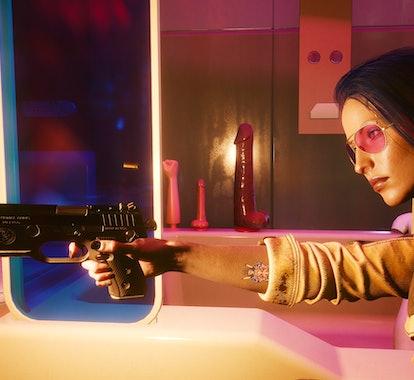 A women firing a gun in front of an assortment of dildos.