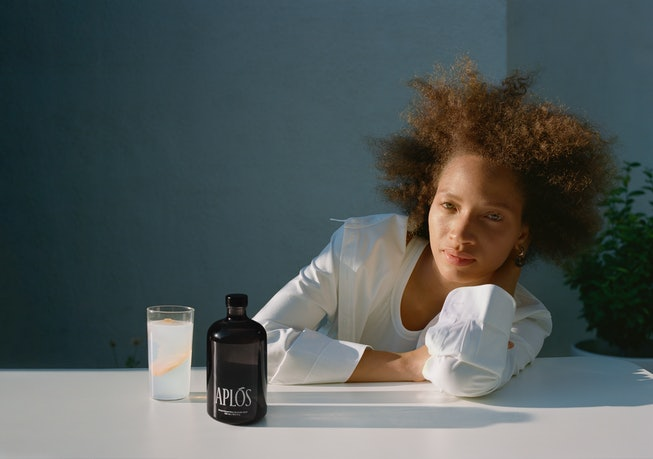 Model posing with bottle of Aplos beverage.