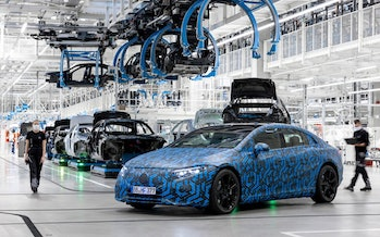 Prototype of the Mercedes-Benz EQS electric sedan parked in a manufacturing plant.