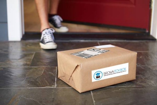 A kid's feet are seen coming out of the house toward a brown package on the porch, labeled Brown Toy Box.
