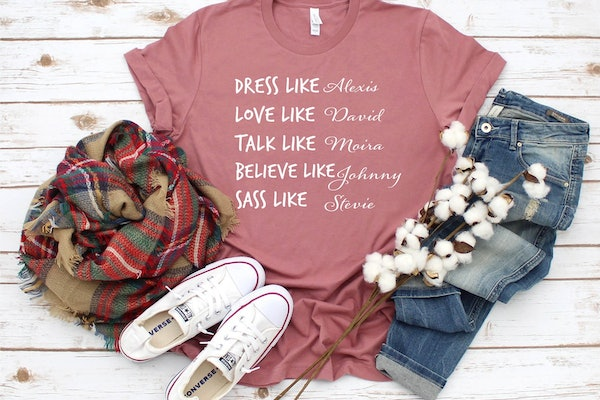 """A 'Schitt's Creek"""" inspired tee sits on the floor with converse sneakers and jeans."""