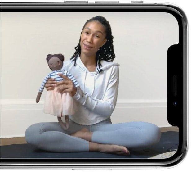 A phone screen shows a woman with braids sitting in a yoga post, holding up a Brown baby doll to the viewer.