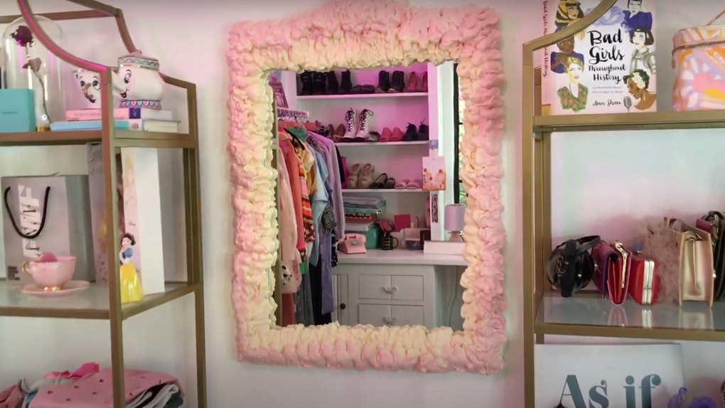 A DIY pink foam mirror sits on the wall next to filled shelves.
