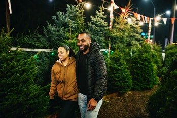 Smiling couple walking through Christmas tree lot while shopping for tree