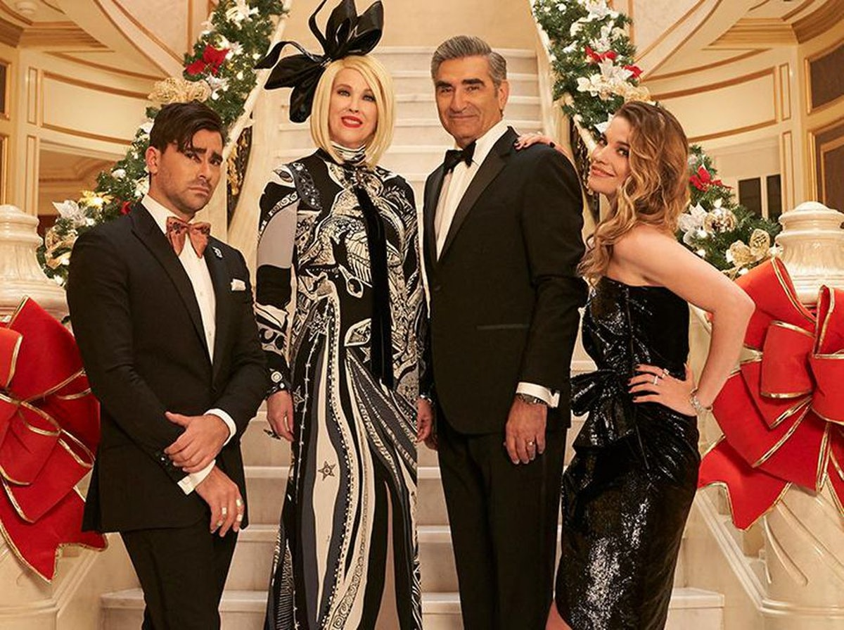 The Rose family from 'Schitt's Creek' stand on their staircase, dressed for a formal holiday party.