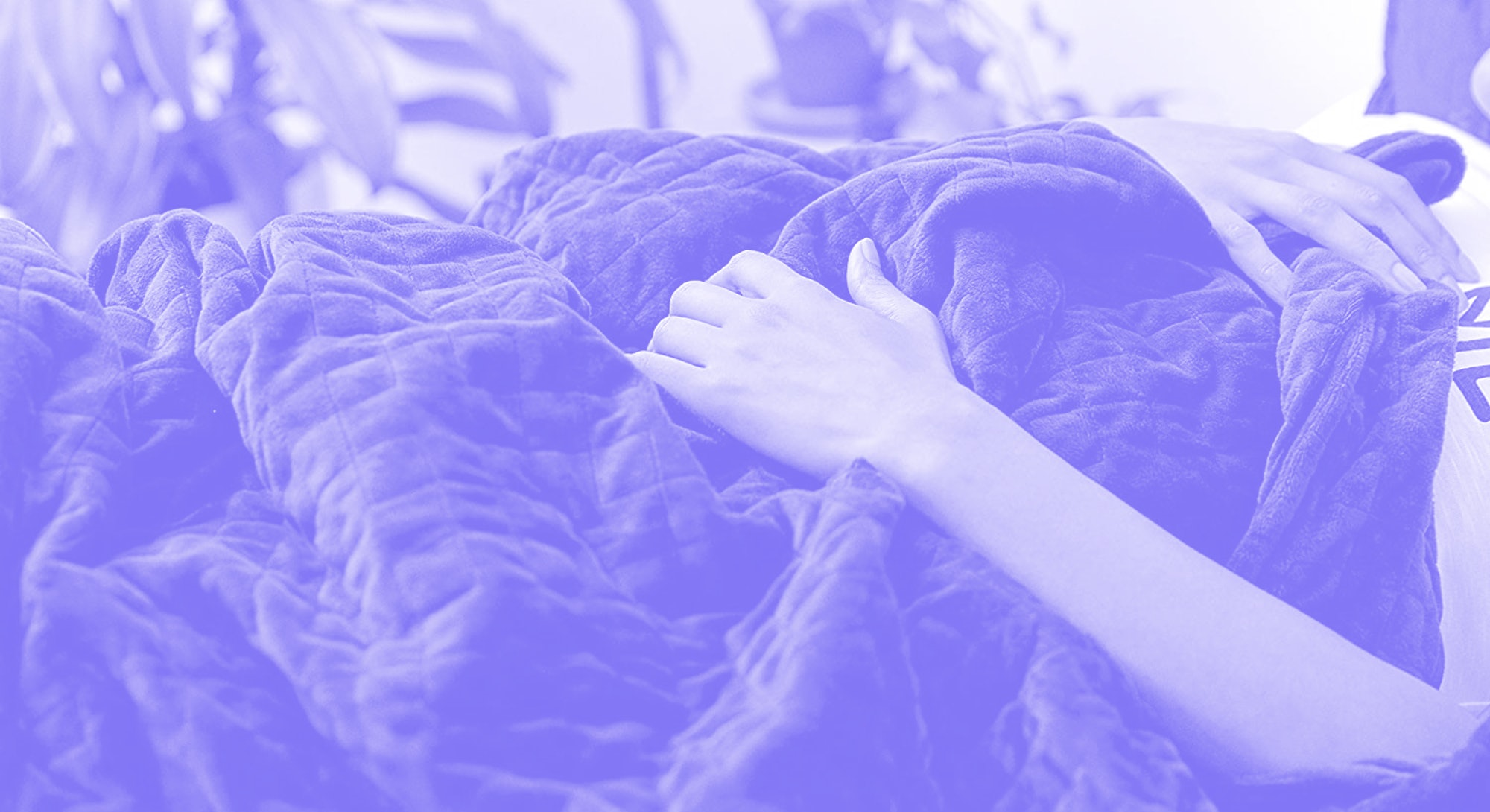 A person lies beneath a navy blue weighted Gravity blanket, their hands on top of the blanket.