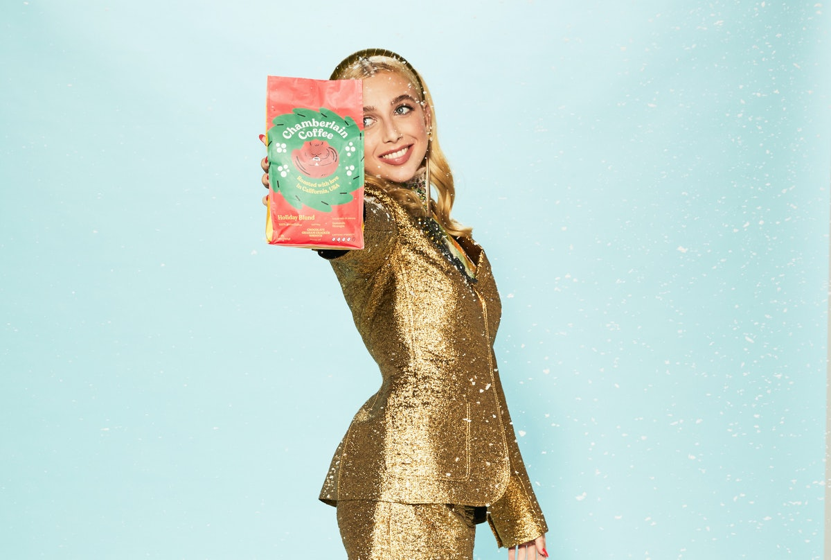 Emma Chamberlain holds up her holiday blend of Chamberlain Coffee while dressed in a gold outfit.