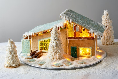 midcentury modern style gingerbread house with a glittery teal roof and light up inner.