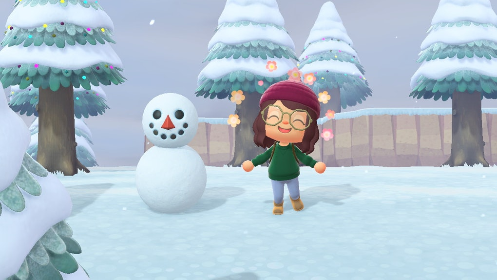 A girl character expresses joy while standing next to a snowboy in 'Animal Crossing: New Horizons'.
