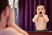 Child pretending to scream in mirror