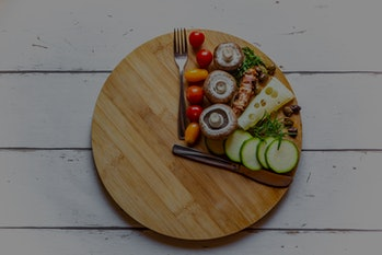 A cutting board in the shape of a clock with a fork and knife as hands and food filling one section