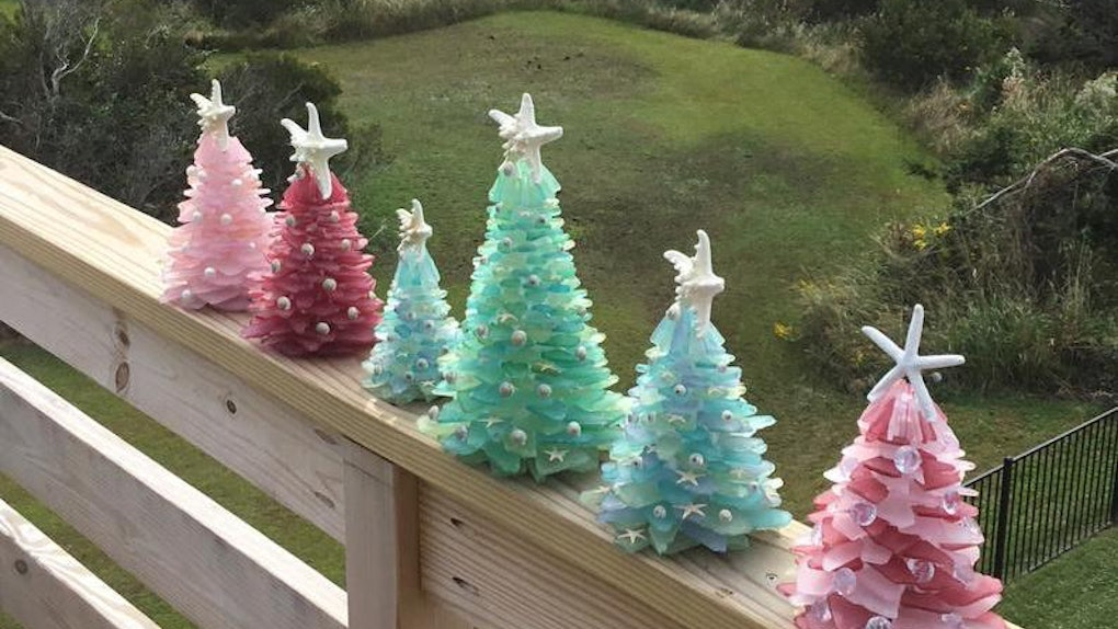 Sea glass Christmas trees line the railing of a back porch overlooking a grassy yard.