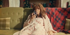 Kristen Wiig slumps on couch in pajamas with a glass of wine.