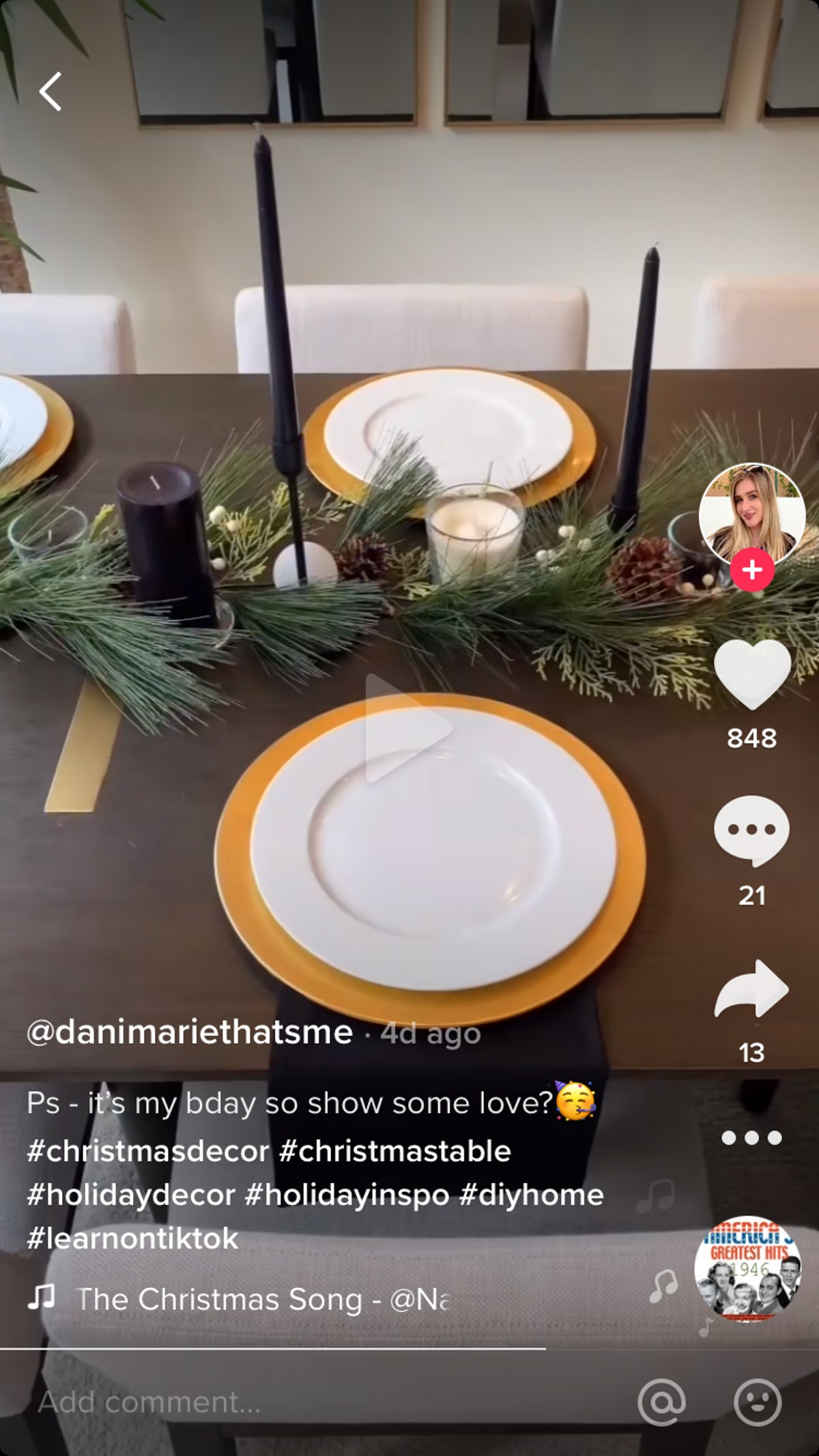 A woman shows how she decorates a modern Christmas table on TikTok, by adding black and white candles next to golden charger plates for an elegant design.
