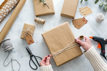 Person wrapping presents in plain brown paper