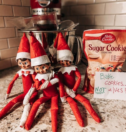 "Three Elf on the Shelf dolls sit on a kitchen counter, variously bandaged, with a sign that reads ""Bake Cookies Not Elves!"""