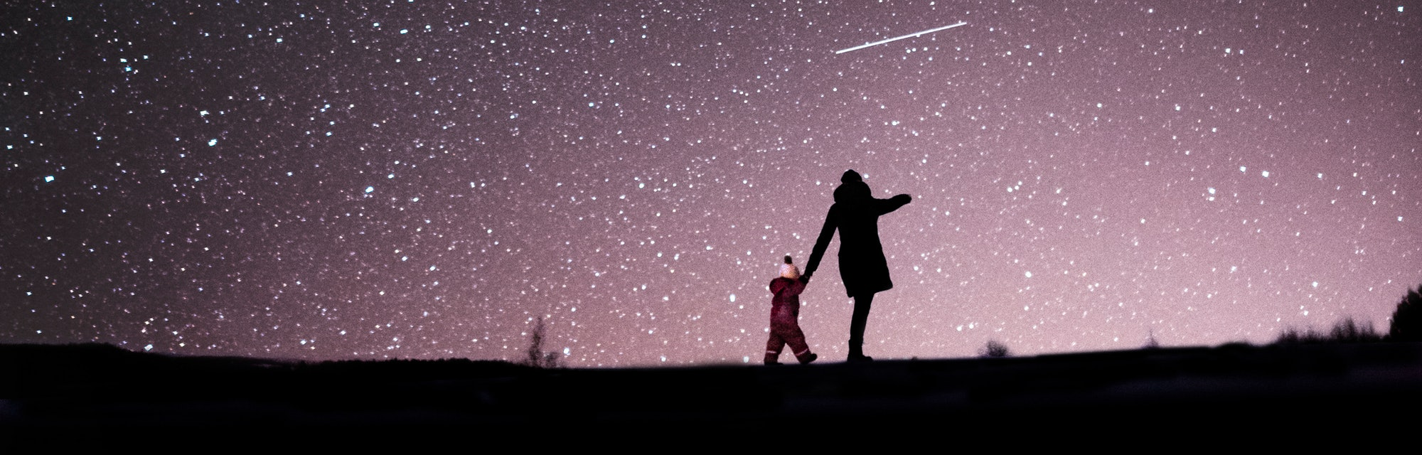 A mother and child in a dark field, seen from afar, under a glorious night sky filled with stars.