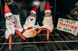 """Three Elf on the Shelf elves sit wrapped in blankets in an oven around a toasted bun with a sign that reads """"It's a lot toastier in here!!"""""""