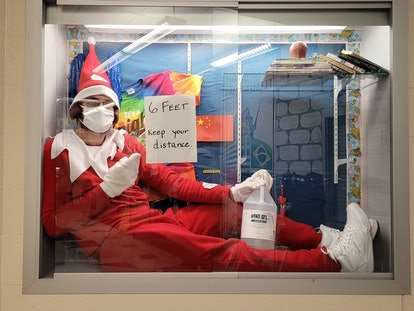Kensington Elementary School Principal Terry Vaughn Jr. poses with hand sanitizer and a sign encouraging social distancing in an Elf On The Shelf Costume inside a glass display case.