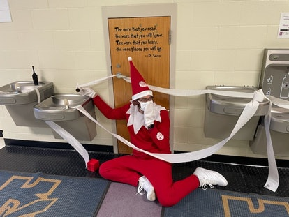 Kensington Elementary School Principal Terry Vaughn Jr. poses between metal drinking fountains that have been wrapped in toilet paper while wearing an Elf On The Shelf costume.