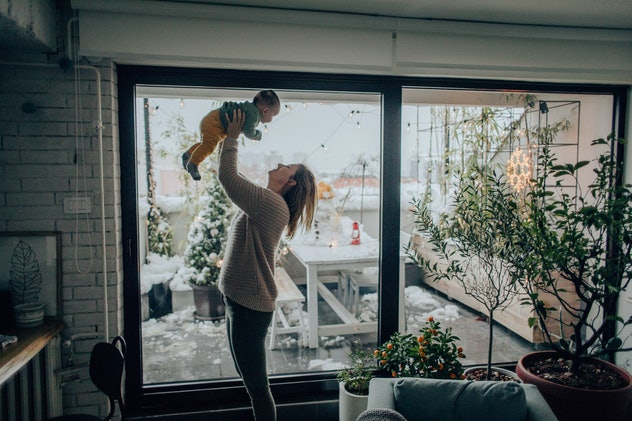 mom holding baby above head in the kitchen