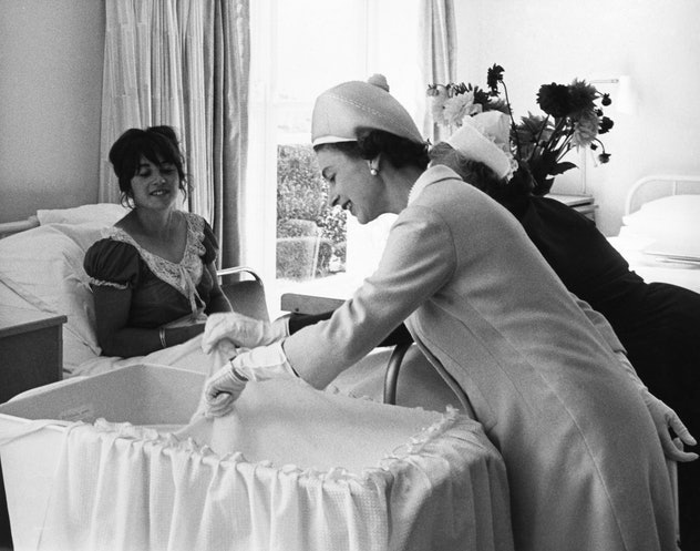 Queen Elizabeth II looking at a baby in the maternity ward.