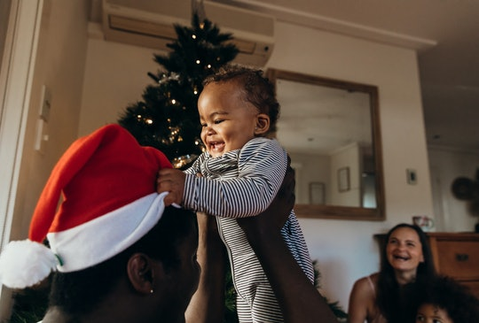parent holding happy baby in front of a christmas tree