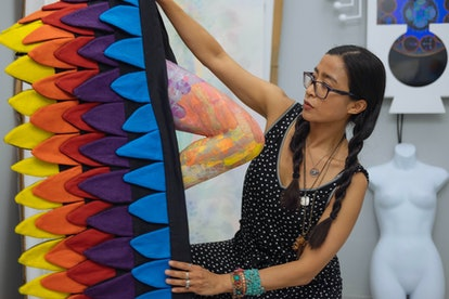 The artist Saya Woolfalk at work in her studio, with a large colorful sculpture.