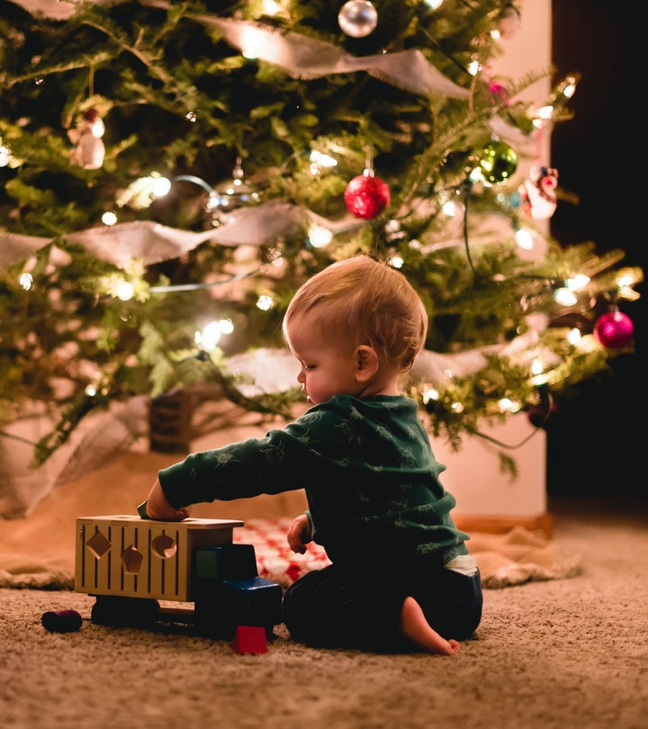 toddler sitting in front of lit up christmas tree, playing with a toy