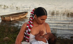 The artist Cynthia Cervantes breastfeeds her baby in front of a beautiful ocean bay.