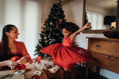 girl spinning around in red dress in front of Christmas tree