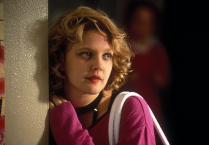 Drew Barrymore with short blonde curls hair in the '90s.