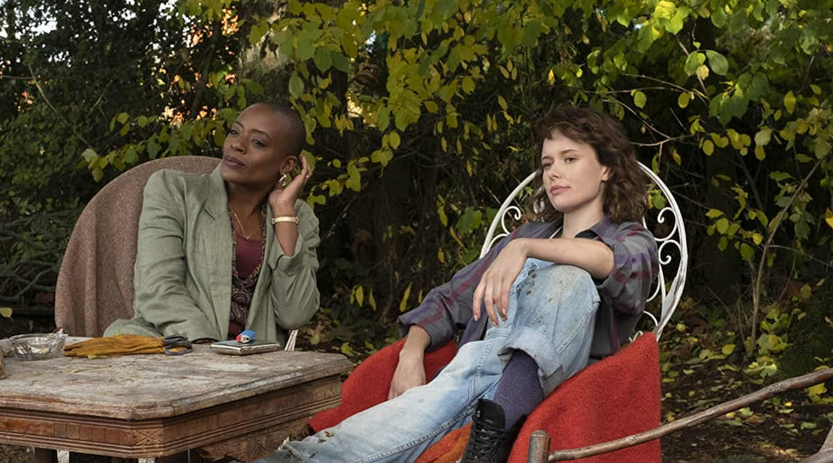 T'Nia Miller and Amelia Eve sit in chairs outside in a scene of 'Haunting of Bly Manor'.