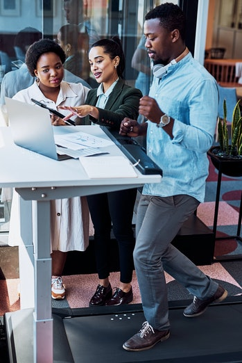 Coworkers meet at a treadmill desk