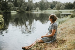 woman in sundress, sitting by a lake