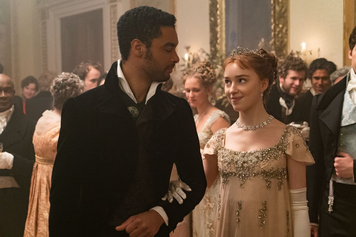 Simon and Daphne look at each other whole attending a ball in 'Bridgerton'.