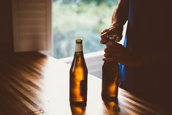 Man opening up a new beer bottle.