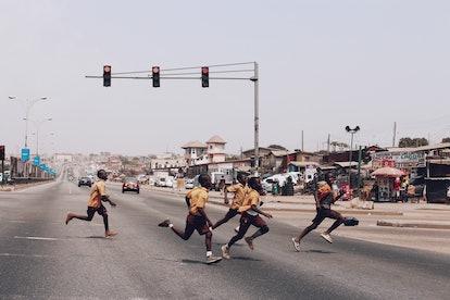 A group of school boys cross the highway. Accra, Ghana.