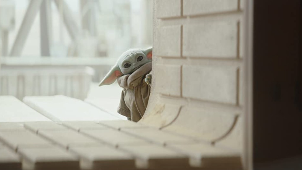 Baby Yoda from Disney's 'The Mandalorian' peaks around a concrete wall.