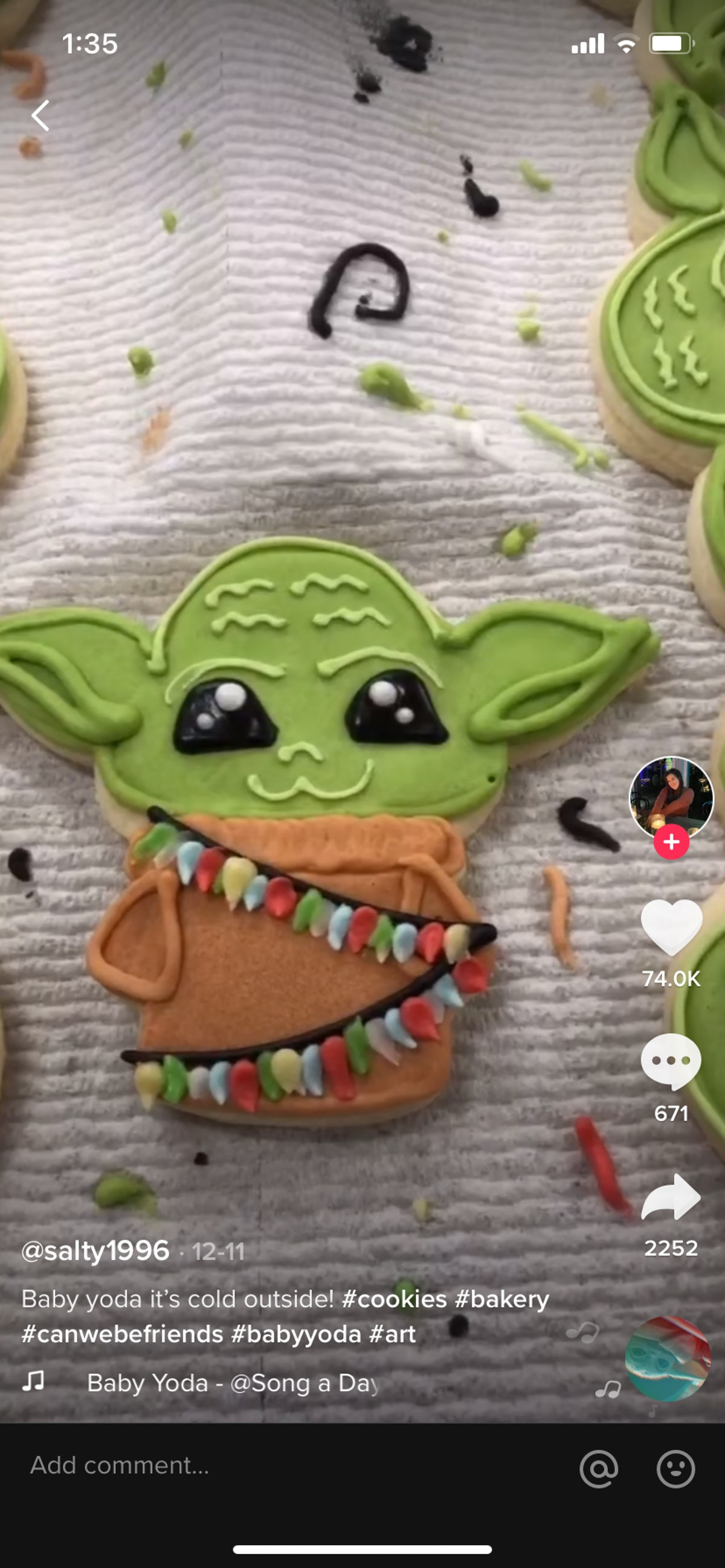 A TikTok user decorates a Baby Yoda cookie with layers of frosting.