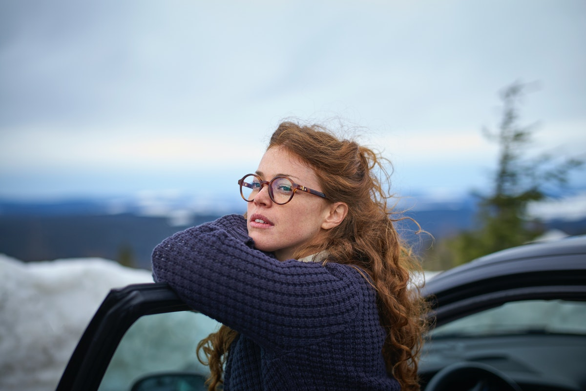 Woman leaning on car in winter